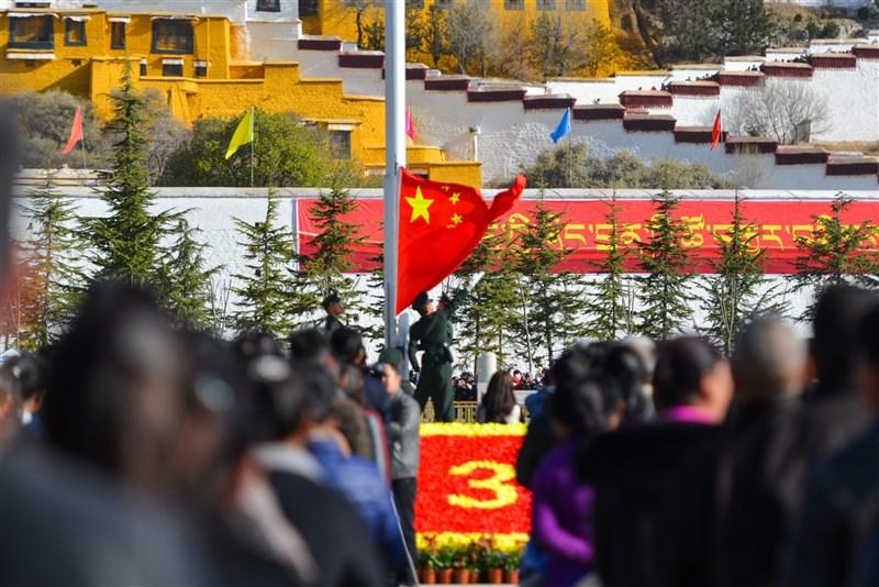 中國西藏自治區政府6日公布與邊境管理有關、被稱為「十五禁」的15項嚴格禁令。圖為西藏各族聚集在拉薩布達拉宮廣場,升中國國旗、唱國歌。(中新社)
