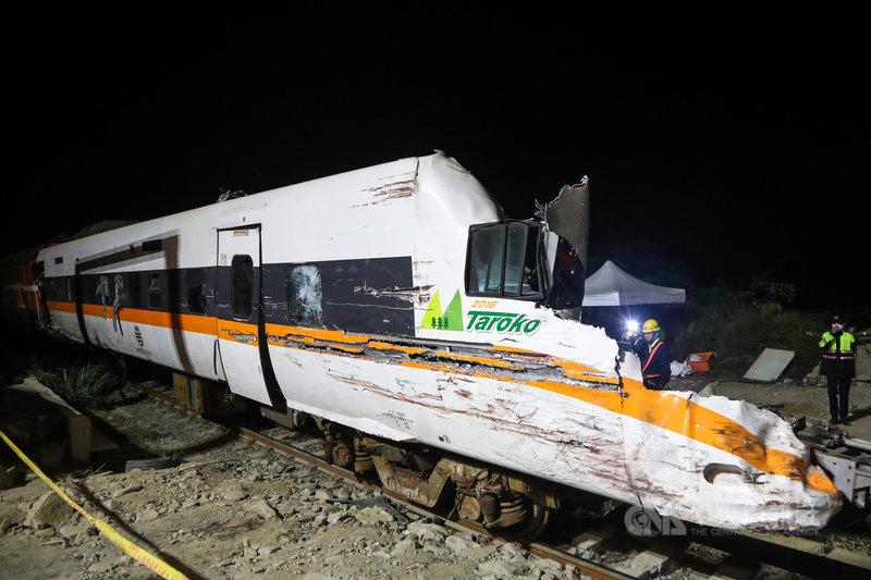 台鐵太魯閣號事故現場持續搶通,7日凌晨工作人員將第8節車廂拖出隧道,可見車頭部分因遭受撞擊嚴重受損。中央社記者王騰毅攝 110年4月7日