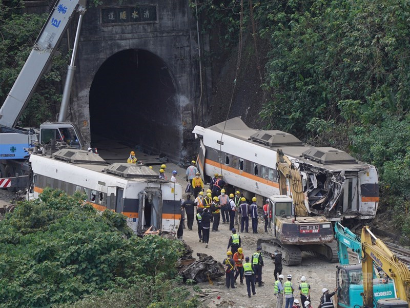 台鐵太魯閣號出軌事故現場持續搶通,6日下午順利拖出受損嚴重的第7節車廂(右),並暫置隧道口進行初步勘查。中央社記者徐肇昌攝 110年4月6日