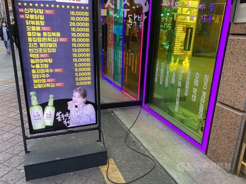 韓國保健福祉部擬修法更嚴加管制酒品廣告,包括限制廣告播出時段,也禁止戶外大型看板刊登酒品廣告,店家使用的小型看板則暫不受限制。圖為餐廳外的看板燒酒廣告及韓國藝人秀智代言照片。中央社記者廖禹揚首爾攝 110年4月10日