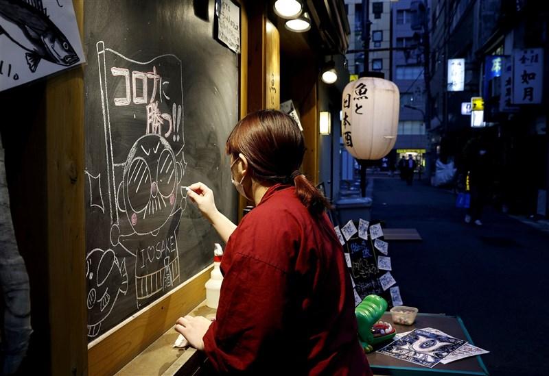日本大阪、東京及沖繩地區疫情持續升溫。8日東京新橋一間餐館店員在店外黑板寫上「戰勝冠狀病毒」字樣。(共同社)