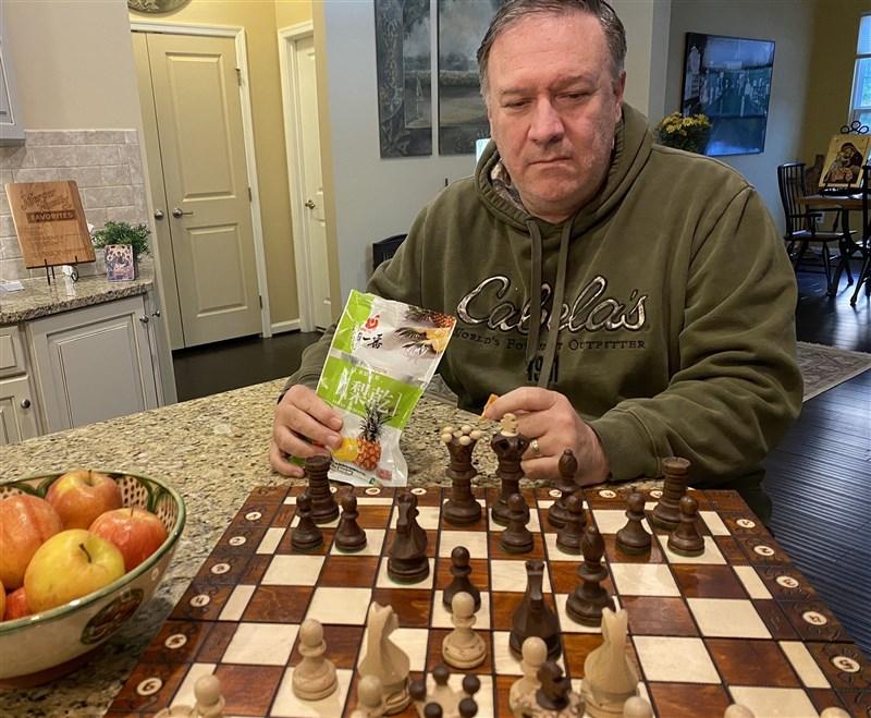 前美國國務卿蓬佩奧11日在推特曬家居照,照片中的他邊下棋邊啖台灣鳳梨乾。(圖取自twitter.com/mikepompeo)