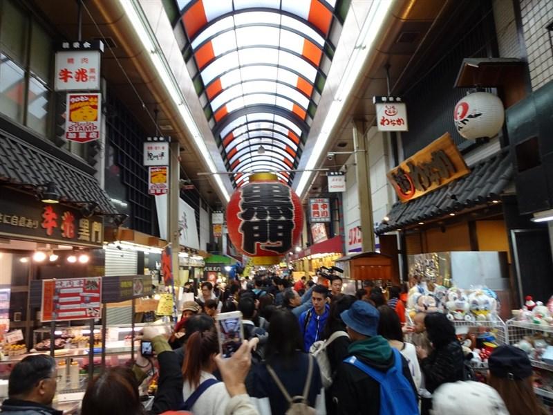 日本大阪黑門市場近日因疫情少了外國客,日本人也不愛去,生意慘淡。圖為黑門市場昔日人潮洶湧情況。(中央社檔案照片)