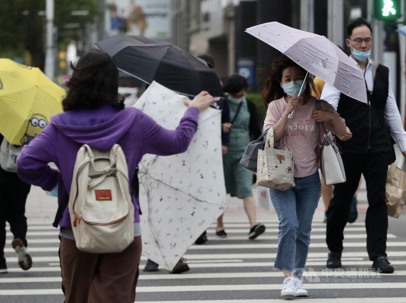 中央氣象局表示,13日白天各地大多為多雲到晴,隨著鋒面通過及東北季風增強,北台灣氣溫會逐漸下降,感受較涼,有局部短暫陣雨。圖為午後台北地區飄下細細雨絲,部分民眾撐傘擋雨。中央社記者張皓安攝 110年4月13日