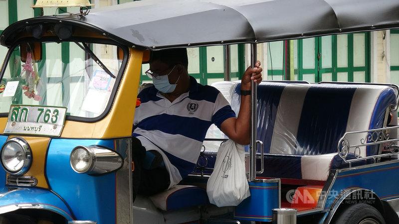 因為武漢肺炎疫情,泰國政府禁止民眾在宋干節期間進行潑水活動,往年擠滿人潮的曼谷考山路商圈冷冷清清,沒有生意的嘟嘟車司機在車上玩手機。中央社記者呂欣憓曼谷攝  110年4月13日