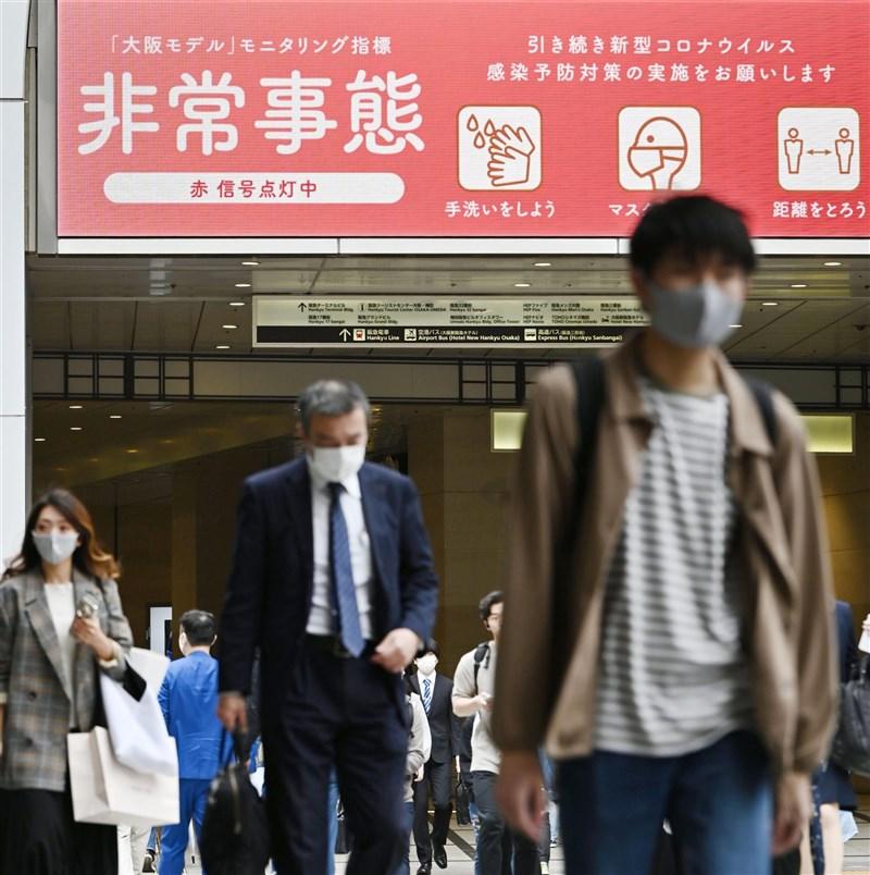 日本武漢肺炎疫情延燒,大阪府13日新增逾千例再創疫情爆發以來當地最高紀錄。圖為大阪車站進出旅客行經大型防疫看板。(共同社)