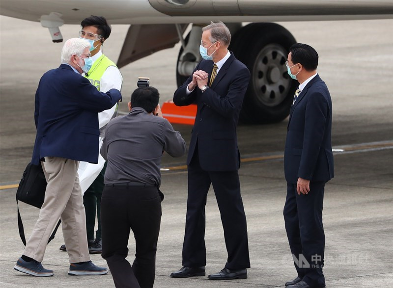 美國總統拜登摯友、前參議員陶德(Chris Dodd)(左白髮者)所率訪問團搭乘專機,14日下午飛抵台北松山機場,外交部長吳釗燮(右)、美國在台協會(AIT)處長酈英傑(William Brent Christensen)(右2)到場接機,酈英傑向陶德拱手致意。中央社記者王騰毅攝 110年4月14日