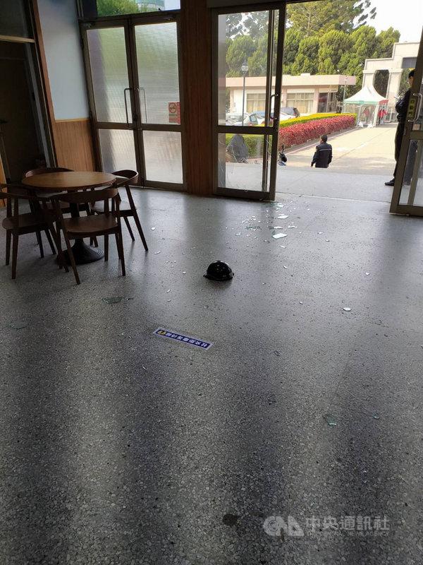 金門縣政府前棟大樓玻璃門14日上午遭民眾砸毀,服務台工作人員查看,發現碎玻璃散滿地,地上還有一頂安全帽,緊急通知警方處理。(民眾提供)中央社 110年4月14日