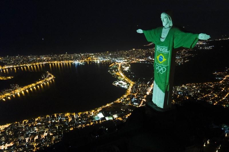 數百台LCD投影機打出光束,將全球著名的巴西救世基督像換裝,標誌東京奧運邁入倒數100天。(美聯社)