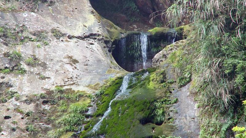 杉林溪森林生態渡假園區的松瀧岩瀑布近來因旱象變成涓涓流水,遊客戲稱水量彷彿水龍頭。園區18日表示,枯水期水量會較小,但今年「巨瀑變涓流」的確是開園以來少見。(翻攝畫面)中央社記者蕭博陽南投縣傳真  110年4月18日