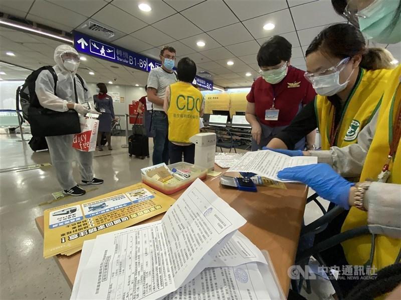 疫情指揮中心宣布19日新增3例武漢肺炎境外移入病例,分別自菲律賓及印度入境。圖為桃園機場防疫人員協助入境旅客填寫資料。(中央社檔案照片)