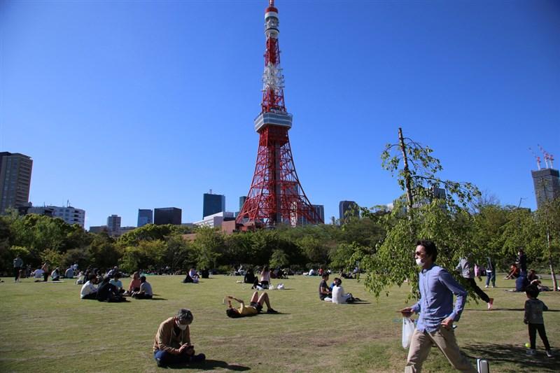 日本網友號召「全國同時無口罩野餐日」活動引發爭議,活動網站已公告取消。圖為東京鐵塔附近公園遊客,非新聞當事人。(中央社檔案照片)