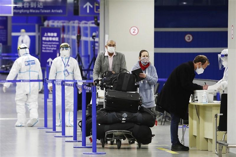 中國駐美國大使館日前發出通知稱,擬赴中國人士若持美製COVID-19疫苗接種紀錄並通過檢測,可正常申請健康碼。圖為上海浦東機場人員著防護衣為入境旅客確認資料。(中新社)