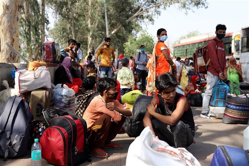 印度疫情失控暴增,19日新德里宣布封城,大量民眾聚集公車站等待返鄉。(安納杜魯新聞社)