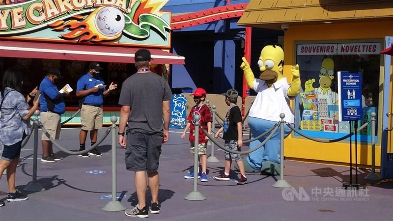 美國南加州的主題樂園4月陸續重新開張,好萊塢環球影城15日以「新常態」迎接遊客,卡通人偶用繩索圍住,遊客合影時須保持距離。中央社記者林宏翰洛杉磯攝 110年4月16日