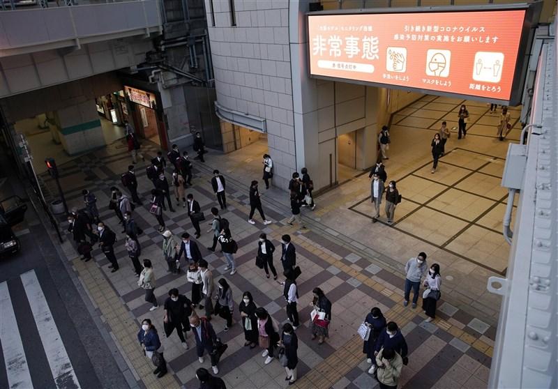 日本政府預定23日晚間將對疫情嚴峻的東京都、大阪府、兵庫縣及京都府4都府縣,正式發布第3度「緊急事態宣言」。圖為大阪民眾22日戴口罩上街。(共同社)