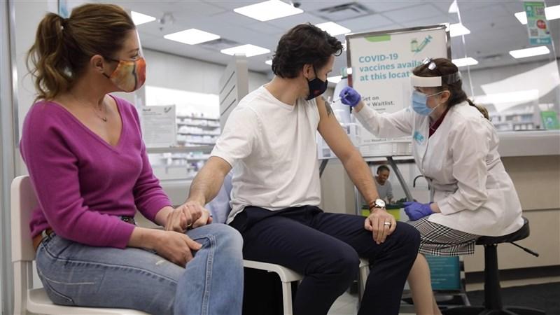 加拿大總理杜魯道(中)23日接種AZ疫苗第一劑,希望帶頭示範接種讓民眾安心。(圖取自facebook.com/JustinPJTrudeau)