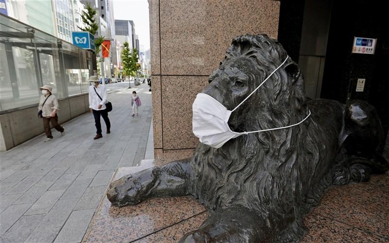 日本東京等4都府縣三度「緊急事態宣言」25日上路,預料將二度迎接「冷清黃金週」。圖為24日銀座街頭一尊獅像被戴上口罩。(共同社)