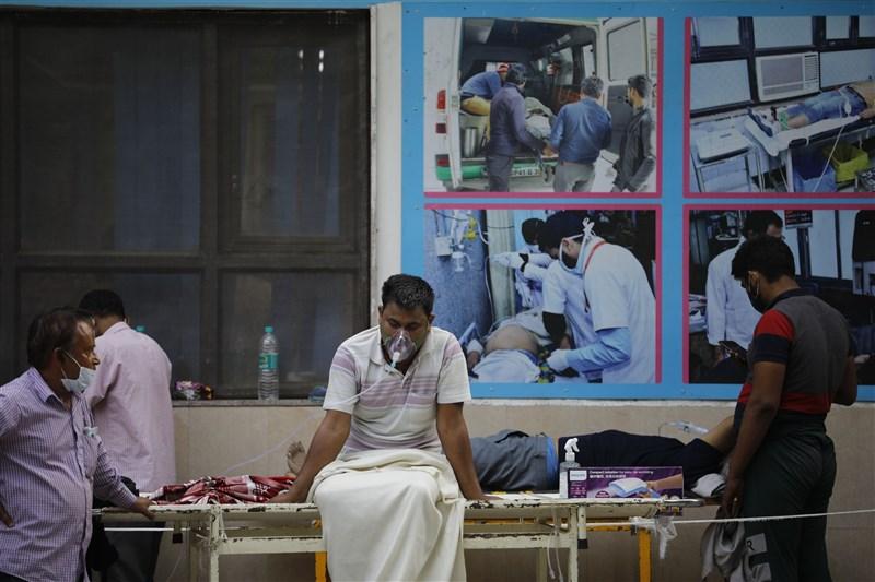 印度疫情發燒,25日新增確診及死亡病例雙雙創下新高。圖為23日新德里數名患者在醫院外的擔架上等待入院。(安納杜魯新聞社)