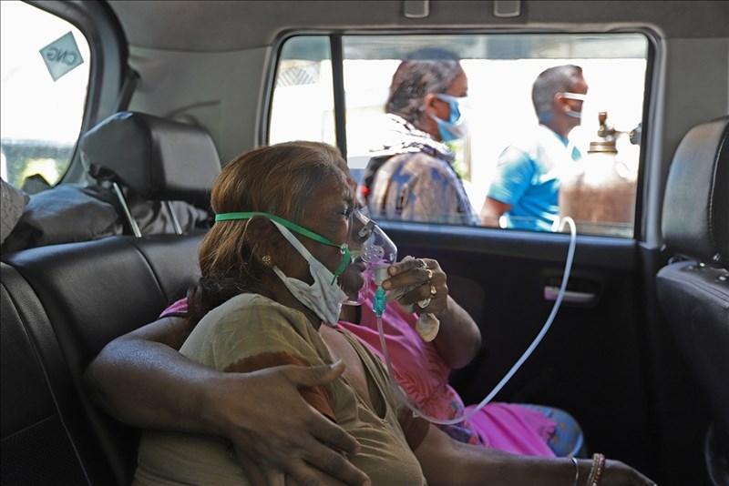 印度武漢肺炎疫情嚴峻,確診者再創新高紀錄。圖為24日印度北方加茲阿巴德染疫民眾在醫院外接受供氧。(安納杜魯新聞社)