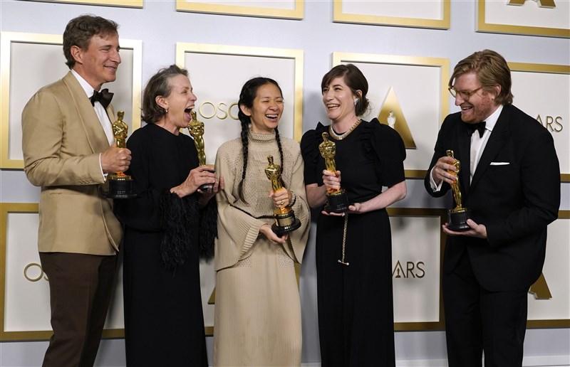 「游牧人生」25日一舉拿下第93屆奧斯卡3座大獎,包括最佳影片、最佳導演和最佳女主角。圖為導演趙婷(中)、女主角法蘭西絲麥朵曼(左2)等人獲獎後合照。(美聯社)