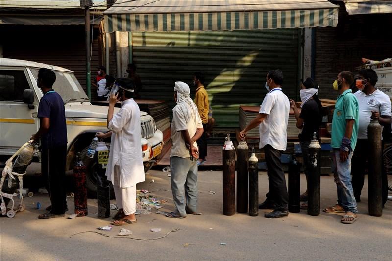 印度COVID-19疫情嚴峻,新增3689人病故再創新高。圖為4月27日病患家屬帶著空的氧氣筒在新德里一處氧氣填灌中心外排隊等候。(安納杜魯新聞社)