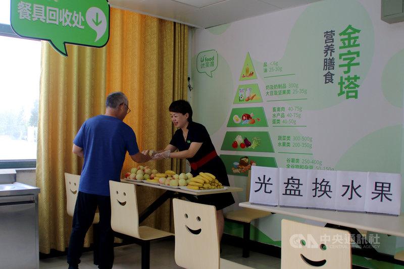 中國人大常委會29日通過「反食品浪費法」,明定若消費者點餐浪費,業者可收廚餘垃圾處理費。圖為去年8月28日,安徽省肥西縣一個機關餐廳裡,工作人員用吃乾淨的「光盤」換水果。(中新社提供)中央社 110年4月29日
