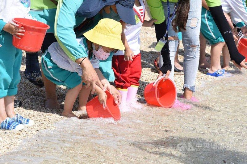 澎湖至美等幼兒園200多名小朋友30日在龍門後灣海灘放流8000尾烏賊苗,讓幼童在親海過程中認識海洋保育,進而愛護海洋,為澎湖的海洋永續與活化注入新生命。(澎湖縣政府提供)中央社 110年4月30日