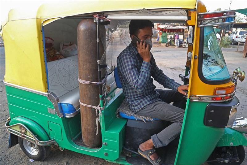 印度疫情惡化,許多染疫民眾因疫情期間沒收入,負擔不起救護車費用,有嘟嘟車駕駛將三輪車改成小型救護車,還備有氧氣瓶。圖為4月30日賈維德.汗改裝的嘟嘟車。(法新社)