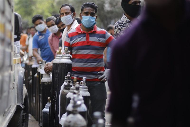 印度疫情沒有好轉,光寶、中橡已把台幹撤回台灣,但也有台幹打算辭職搭機返台。圖為3日在首都新德里等待氧氣筒充氣的民眾。(安納杜魯新聞社)