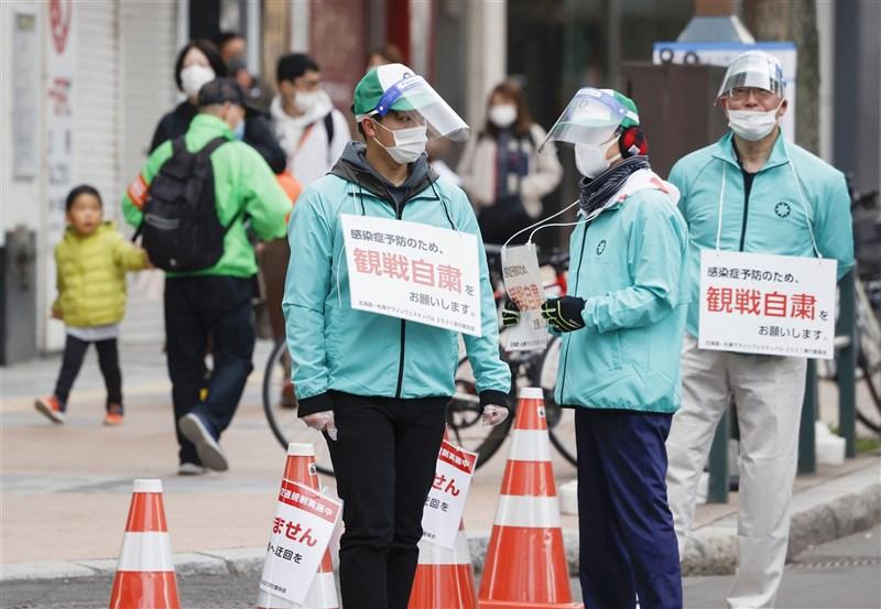 日本政府正研擬延長實施緊急事態,考量將北海道等處納入防止蔓延等重點措施。圖為5日北海道舉行東京奧運馬拉松測試賽,工作人員以告示提醒觀眾賽事不開放參觀。(共同社)