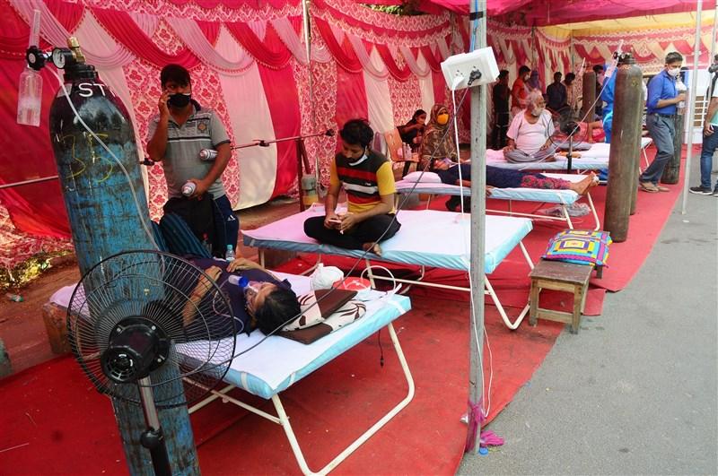 2020年身為抗疫表率的亞洲國家,如今卻面臨疫苗短缺;由於國內未能研發和製造疫苗,許多亞洲國家必須等待歐美供貨。圖為印北加茲阿巴德染疫民眾在一處臨時搭建站接受供氧。(安納杜魯新聞社)