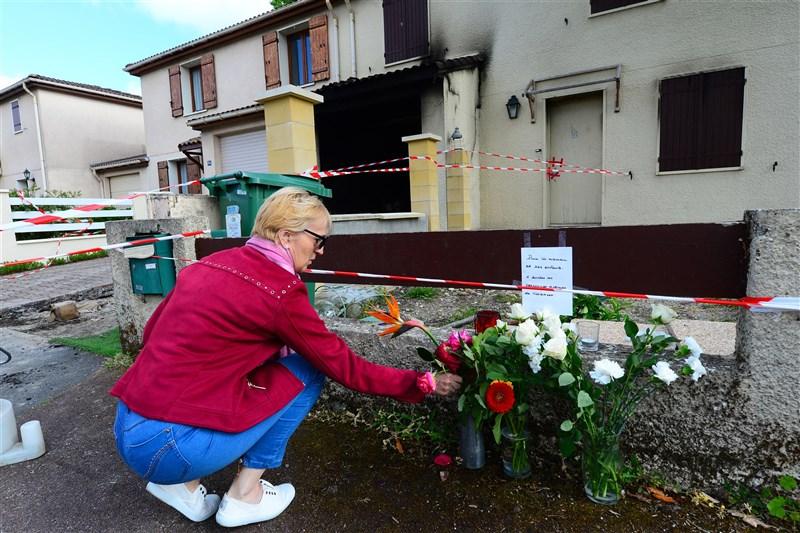 法國一名家暴累犯坐牢9個月出獄後多次騷擾跟蹤妻子,4日在光天化日下開槍射擊妻子,隨後潑灑易燃液體將受害者活活燒死。圖為民眾在受害者被燒毀的住處外獻花哀悼。(法新社)