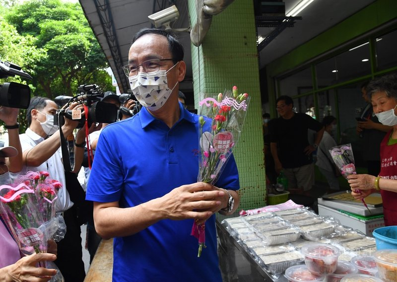 國民黨8日在台北內湖傳統市場舉辦「寵愛媽咪、響應828公投」活動,前國民黨主席朱立倫(中)出席,向民眾分送康乃馨。中央社記者王飛華攝  110年5月8日