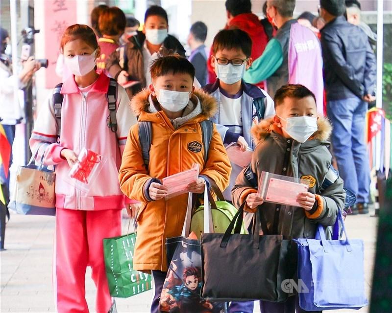 武漢肺炎疫情11日新增7例本土案,台北市提升防疫等級,除了大型活動停辦,畢業旅行及戶外教學、老人共餐也停辦。圖為學生進入校園時戴上口罩、落實防疫。(中央社檔案照片)