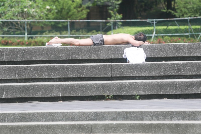 氣象專家吳德榮表示,天氣炎如盛夏至17日,預估要到18日才有鋒面南移。圖為10日民眾在公園打赤膊曬日光浴。中央社記者吳家昇攝 110年5月10日