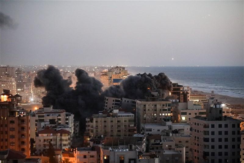 加薩走廊一棟13層樓高住宅大樓遭以色列空襲擊中後於12日晚間倒塌。(安納杜魯新聞社)