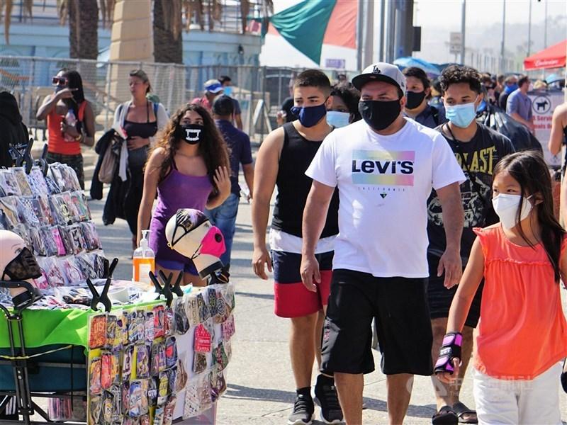 世界衛生組織14日表示,民眾即便已接種了COVID-19疫苗,處於病毒正在蔓延的地區仍須戴上口罩。圖為美國洛杉磯海灘遊客戴口罩行經賣口罩的小販。(中央社檔案照片)