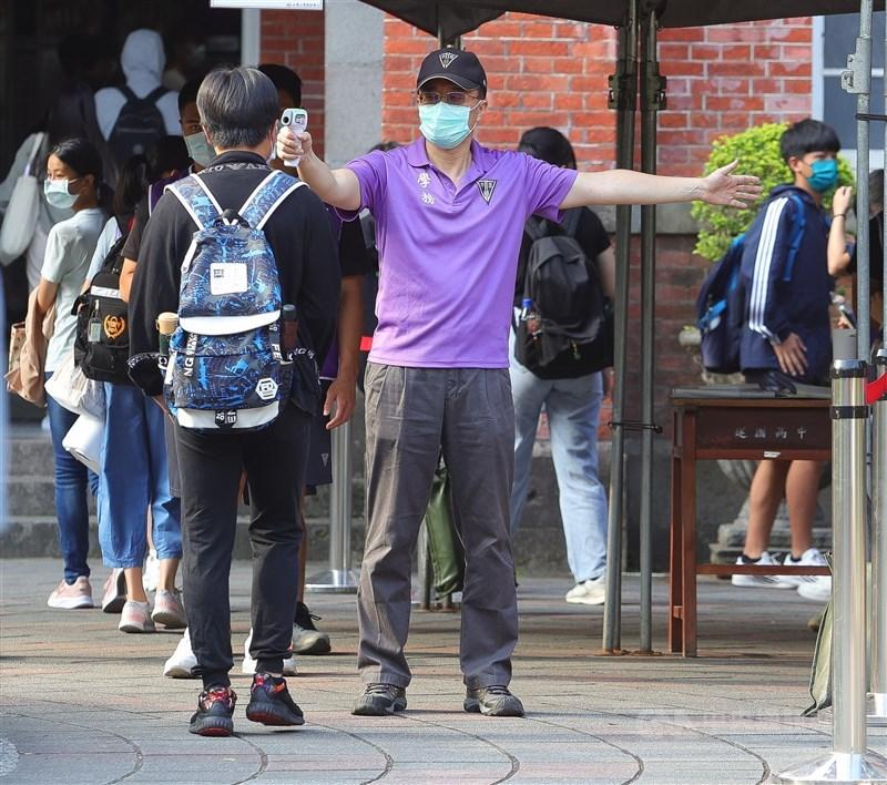 國中教育會考15日登場,配合防疫,考生進入考場前須排隊量測體溫。中央社記者謝佳璋攝 110年5月15日