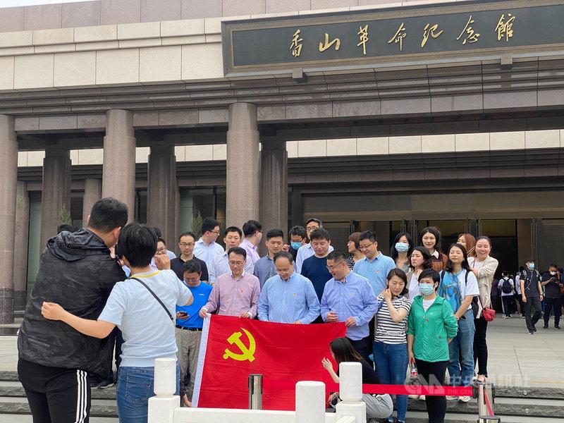 時值中共百年黨慶,北京香山革命紀念館人潮紛至沓來,從國家機關到小學生,可謂「黨政軍民學」全動員。圖為手持中共黨旗合影的參訪機關團體。中央社記者繆宗翰北京攝  110年5月16日