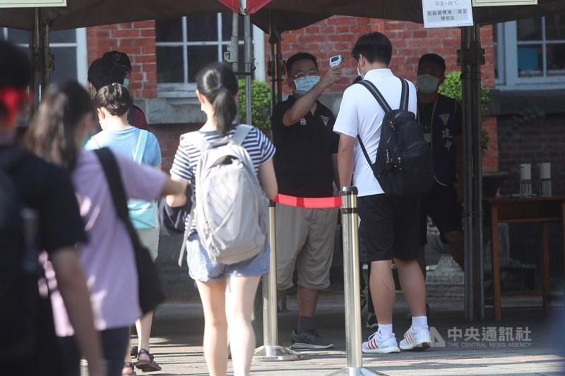 國中教育會考16日第2天,依序考自然、英語閱讀、英語聽力。考場依防疫規定實施體溫量測管制,工作人員幫考生量額溫。中央社記者吳家昇攝 110年5月16日