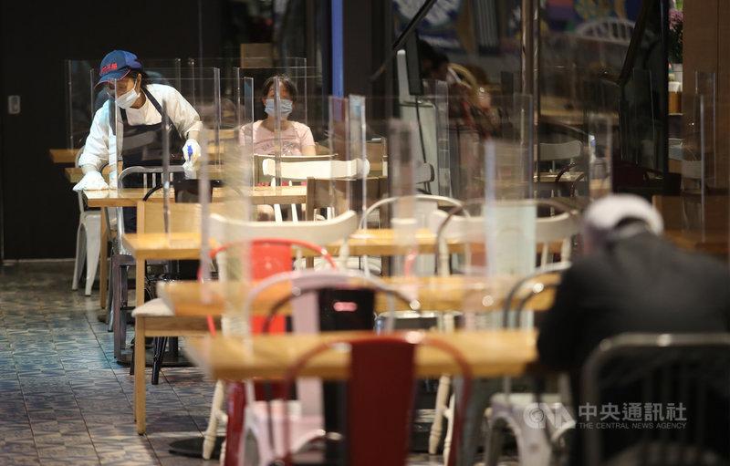 國內武漢肺炎疫情持續升溫,全民防疫神經緊繃。百貨公司美食街除在用餐區桌面擺上隔板,工作人員也隨時清潔環境、加強消毒。中央社記者張新偉攝 110年5月16日