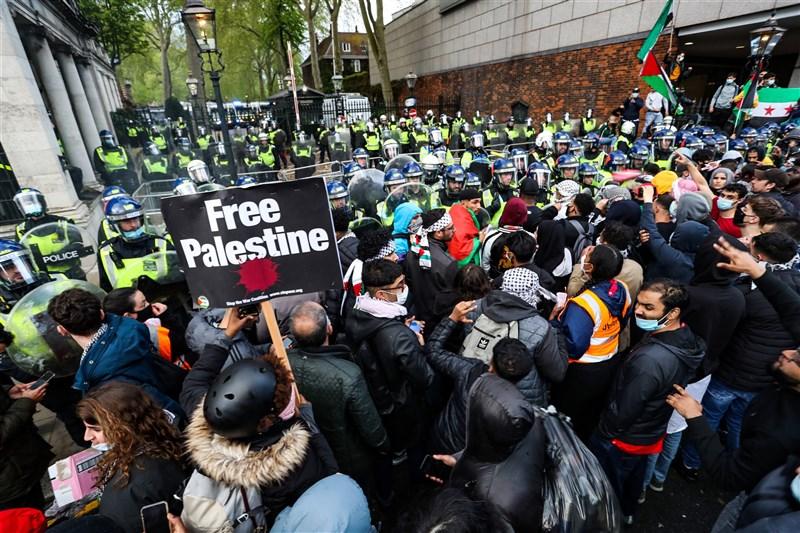 以色列和加薩走廊(Gaza)武裝分子爆發數十年來最暴力的衝突之際,英國各地有多場遊行,15日倫敦示威者高舉「解放巴勒斯坦」標語。(安納杜魯新聞社)
