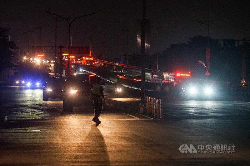 台電表示,17日下午至今用電量持續攀升,全台再次分區限電,目前暫定晚間8時50分開始C、D組進行第一輪限電,影響戶數為66萬戶,時間為50分鐘,限電量150萬瓩,並視後續復電情況進行滾動調整。圖為台北市民權大橋內湖端,在晚間9時停電,路口一片漆黑。中央社記者裴禛攝 110年5月17日