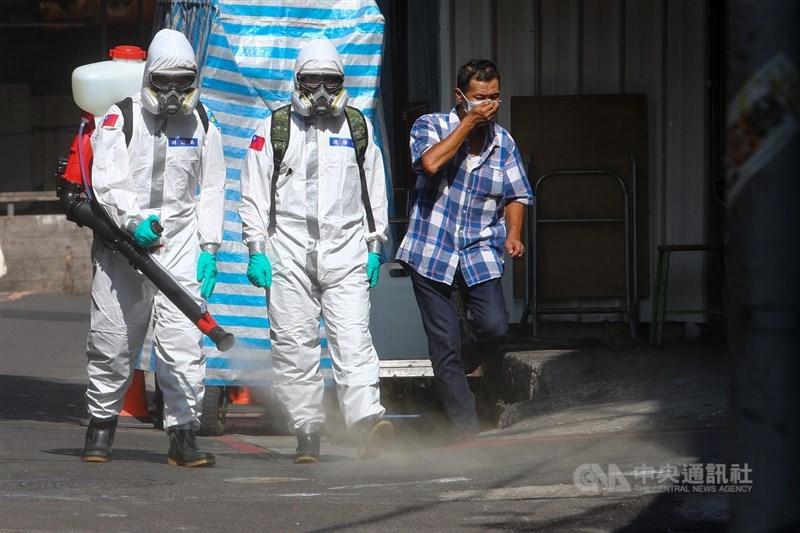 台北市萬華區一名男子經員警勸導後仍不戴口罩,遭開罰8000元罰鍰。圖為16日化學兵沿著萬華街道噴灑消毒水,民眾見狀捂嘴快步避開。(中央社檔案照片)