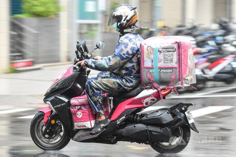 國內疫情升溫,為防群聚,民眾使用美食外送平台需求增加。台北市18日午後下起大雨,外送員全副武裝,在風雨中接單送貨。中央社記者鄭清元攝  110年5月18日