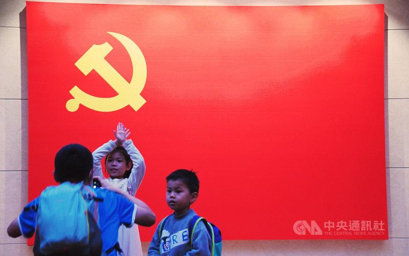 路透社引述消息人士稱,中國可能在未來3到5年全面放開生育政策,但也擔憂這可能使城鄉生育率失衡,增加貧困和就業壓力。圖為2名小孩在位於上海的中共二大會址黨旗前合照。中央社記者沈朋達上海攝  110年5月18日