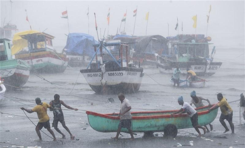 強烈氣旋陶特襲擊印度,造成孟買外海一艘船隻沉沒,船上載有273人,目前有146人獲救,還有127人下落不明。圖為印度漁民試圖將漁船拉至安全地方躲避氣旋。(美聯社)