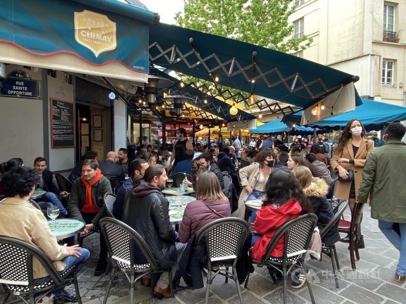 法國解封第二階段19日上路,餐廳酒吧戶外區大爆滿。因為防疫,法國餐廳酒吧自2020年11月起不得內用,至今近7個月。服務生向中央社表示,「小孩都可以生出來了」,以幽默表達無奈。中央社記者曾婷瑄巴黎攝 110年5月20日