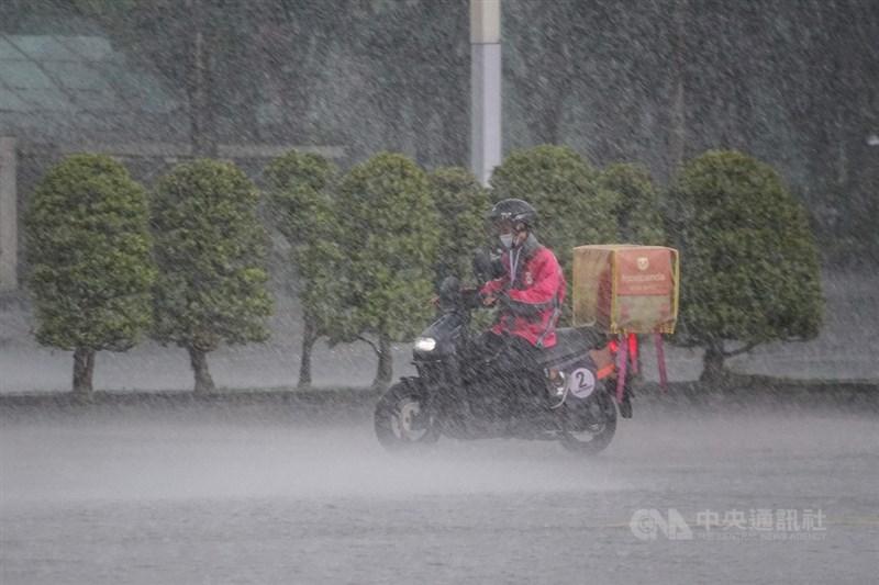 台北市政府宣布24日起所有飲食店、飲料店全面禁止內用,外送與外帶需求增加。下午台北市區下起大雨,外送人員冒雨騎車送單。中央社記者裴禛攝 110年5月24日